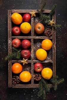 Drewniane pudełko z pomarańczą, jabłkiem i szyszkami ze świątecznymi dekoracjami