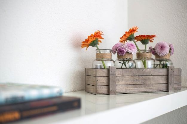 Drewniane pudełko z pomarańczowymi i różowymi kwiatami na białej półce