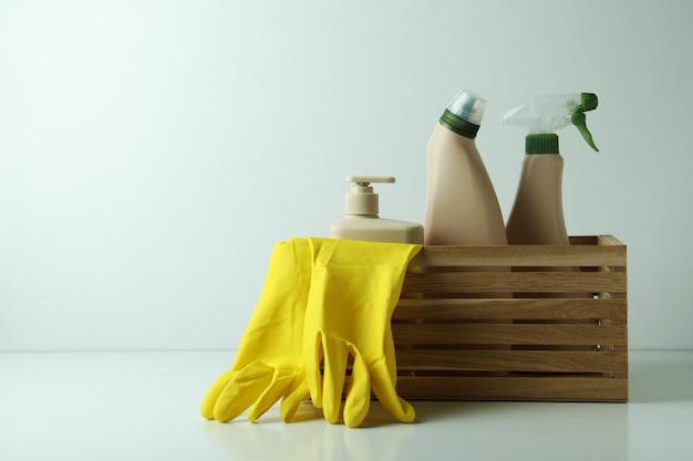 Drewniane pudełko z przyjaznymi dla środowiska narzędziami do czyszczenia na białym stole