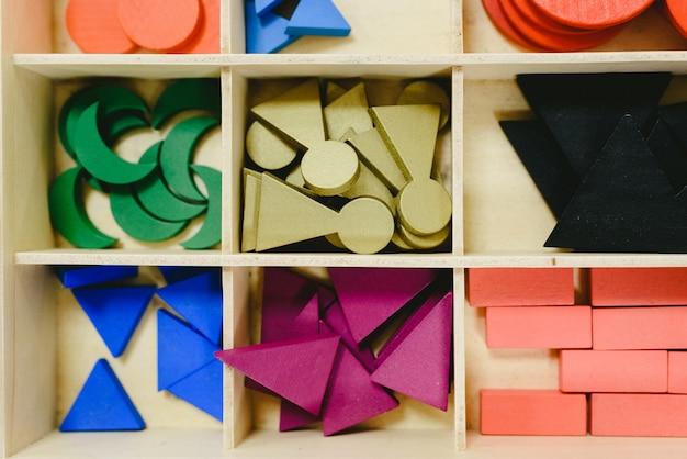 Drewniane pudełko z różnymi materiałami w klasie montessori.