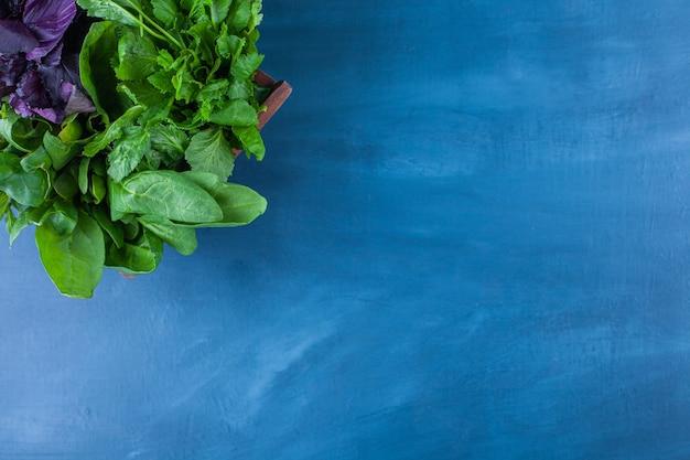 Drewniane pudełko zdrowej zieleni na niebieskim stole.