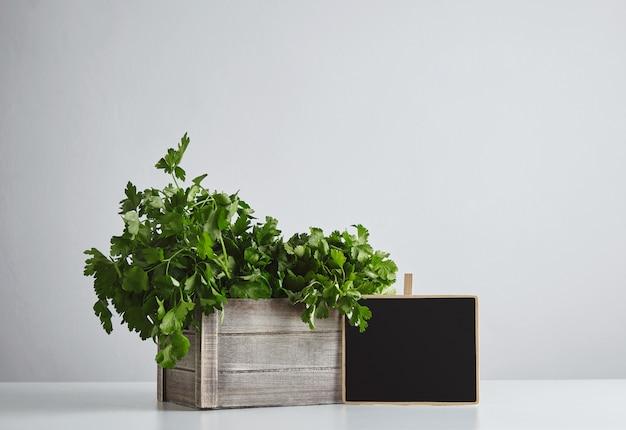 Drewniane pudełko ze świeżą zieloną pietruszką i kolendrą z ceną tablicy kredowej na białym tle na widok z boku biały stół