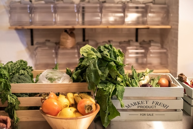 Drewniane pudełko ze świeżymi warzywami i innymi składnikami do gotowania.