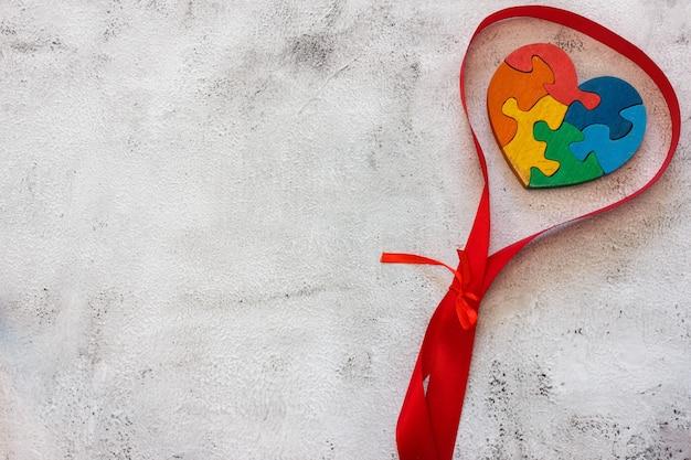 Drewniane puzzle wielokolorowe w kształcie serca na szarym tle. koncepcja walentynki, związek. miejsce na tekst