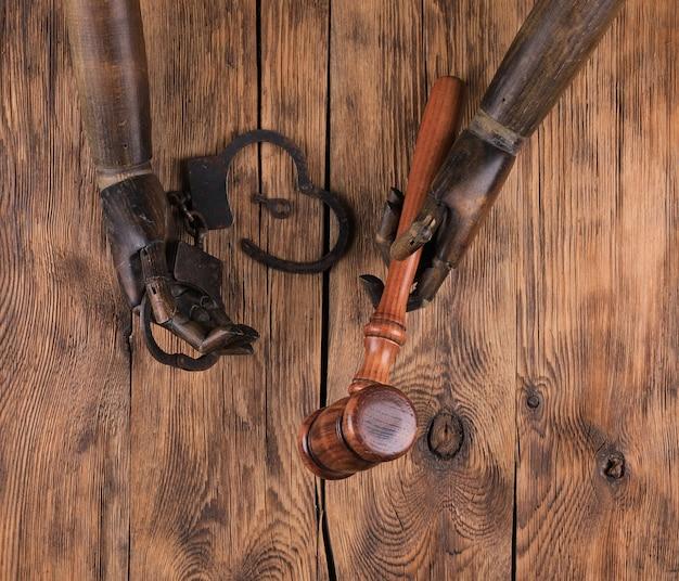 Drewniane ręce manekina i młotek prawniczy