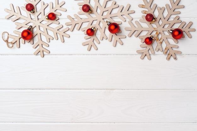 Drewniane rzeźbione płatki śniegu z czerwonymi bombkami na białym tle drewnianych, widok z góry