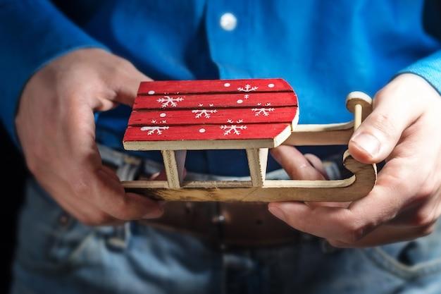 Drewniane sanki z zabawkami i rękami młodego mężczyzny