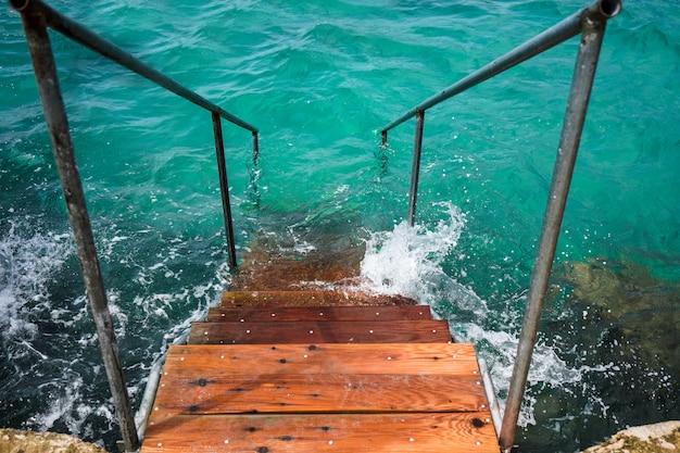 Drewniane schody do krystalicznej turkusowej wody na morzu jońskim, saranda, albania