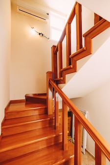 Drewniane schody z balustradami w domu z białymi ścianami, oknem i klimatyzacją