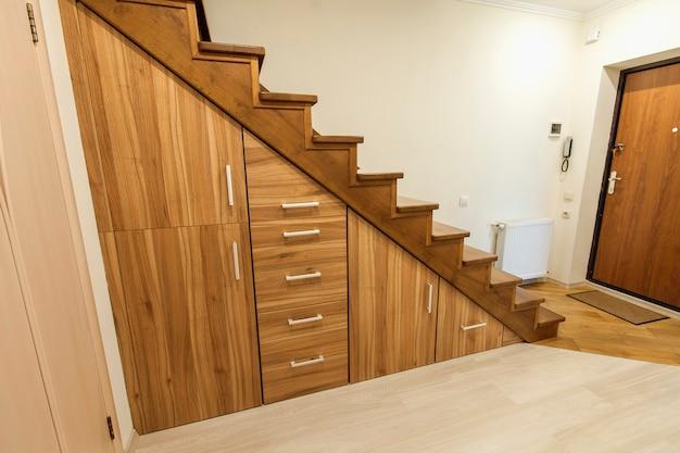 Drewniane schody z niestandardowymi szafkami wysuwanymi.