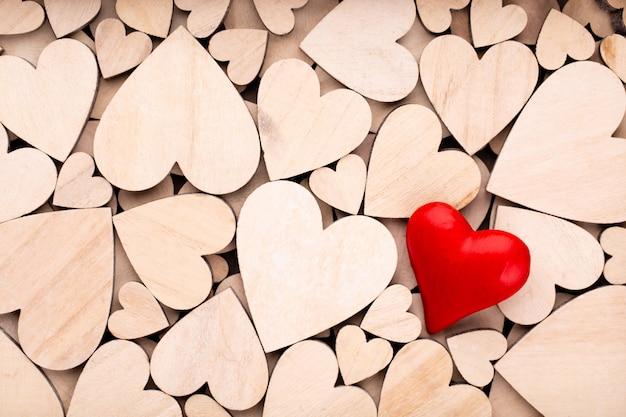 Drewniane serca jedno czerwone serce na powierzchni drewnianych serc