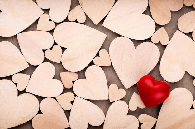 Drewniane serca, jedno czerwone serce na tle drewniane serce.