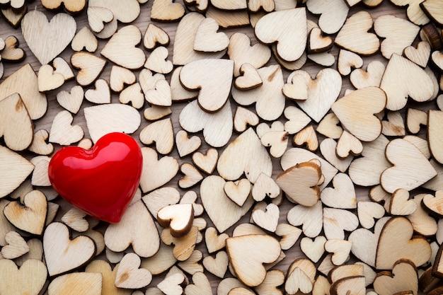 Drewniane serca, jedno czerwone serce na tle serca.