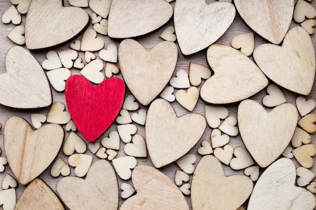 Drewniane serca, jedno czerwone serce na tle serca