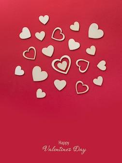 Drewniane serca na pastelowym czerwonym tle. abstrakcjonistyczny tło z drewnianymi kształtami