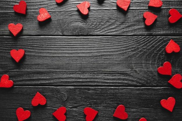 Drewniane serca tworzące granicę na rustykalnym tle drewna. karta walentynki.