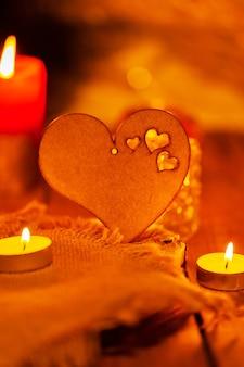 Drewniane serce i świece. walentynki kartkę z życzeniami ze świecą i sercem. koncepcja historii miłości