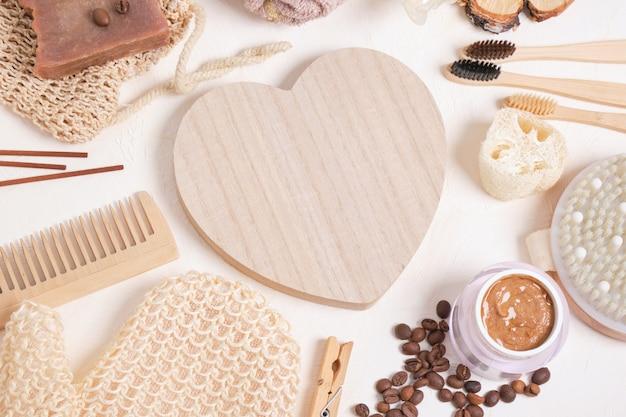 Drewniane serduszko i ekologiczne produkty higieniczne do pielęgnacji i higieny, akcesoria łazienkowe wykonane z naturalnych materiałów na beżowym tle, styl życia zero waste