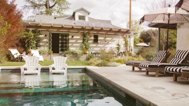 Drewniane siedziska przy basenie z parasolami