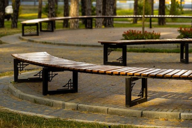 Drewniane siedziska z żelaznymi nogami do wypoczynku w parku