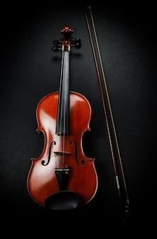 Drewniane skrzypce umieszczone obok łuku, przedstawiają przód instrumentu smyczkowego, na ścianie z czarnego płótna