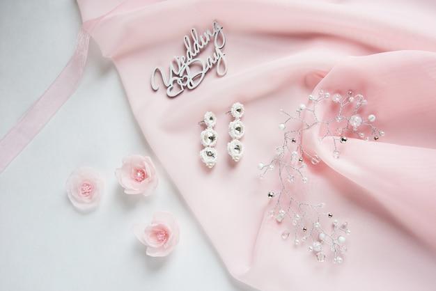 Drewniane słowa weselne, ozdobne kwiaty z tkaniny, biżuteria ślubna na różowej tkaninie