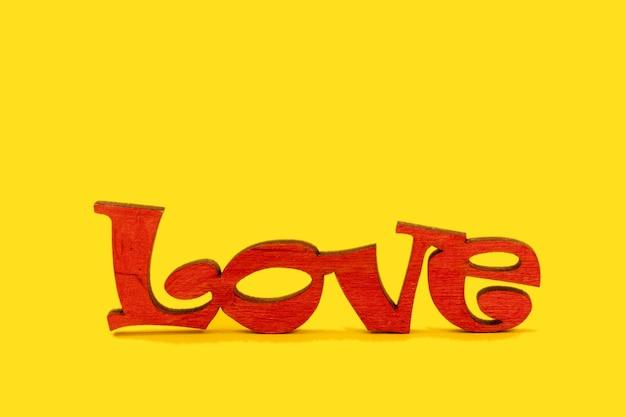 Drewniane słowo miłość na żółtym tle. koncepcja walentynki.