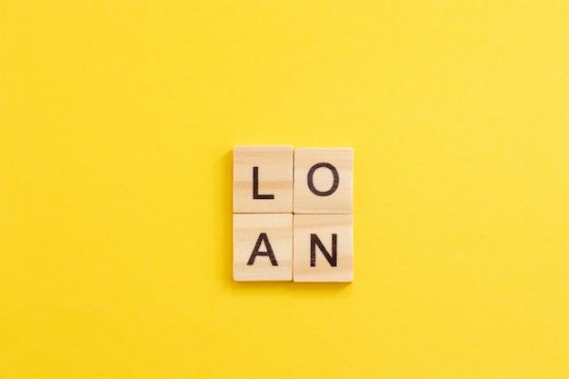 Drewniane słowo pożyczka. koncepcja zakupu zadłużonego mieszkania lub domu.