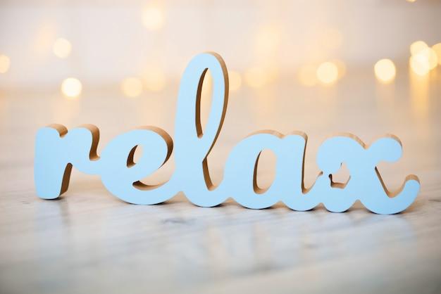 Drewniane słowo relaksuje na łóżku z żółtymi zamazanymi światłami