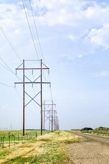 Drewniane słupy elektryczne z błękitnym niebem