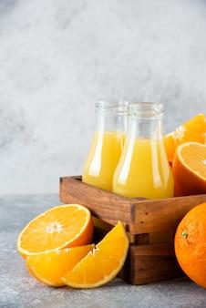 Drewniane stare pudełko pełne pomarańczowych owoców i szklanych dzbanów soku na kamiennym stole.