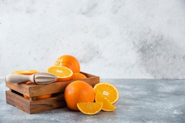 Drewniane stare pudełko pełne soczystych pomarańczowych owoców na kamiennym stole.