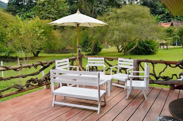 Drewniane stoły, białe krzesła w ogrodzie.