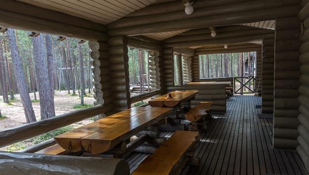 Drewniane stoły i ławki na tarasie domu z bali w lesie