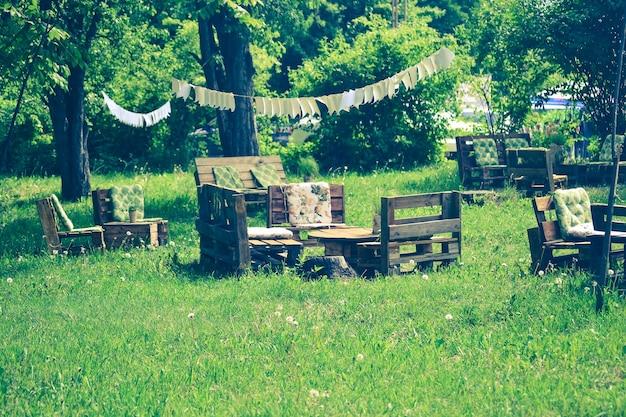 Drewniane stoły i siedziska w ogrodzie