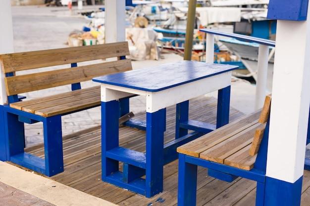 Drewniane stoły z krzesłami do wypoczynku na nabrzeżu
