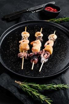 Drewniane szaszłyki z krewetkami, ośmiornicami, kalmarami i małżami. kebab z owocami morza ..