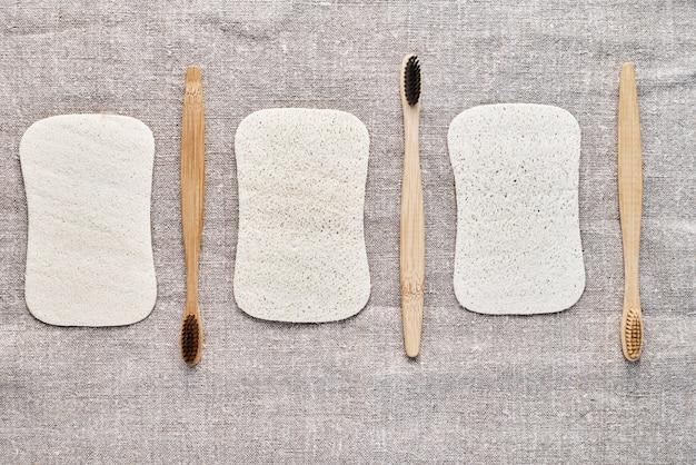 Drewniane szczoteczki do zębów i naturalne myjki na szarym tle lnianym