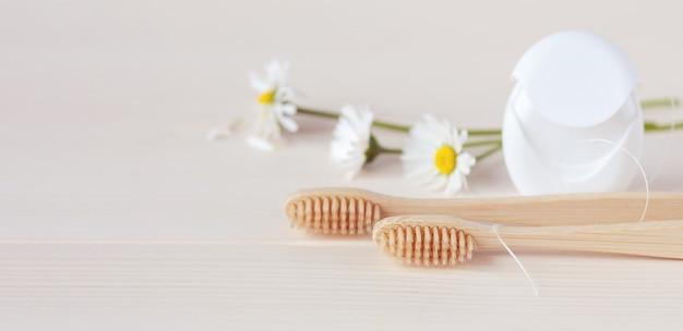 Drewniane szczoteczki do zębów, nici dentystyczne i białe stokrotki na stole