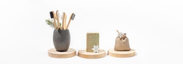 Drewniane szczoteczki do zębów w szarym kubku, naturalne mydło w kostce, gałązka jodły, tekstylne etui, białe płatki śniegu na drewnianych pniakach na białym tle.