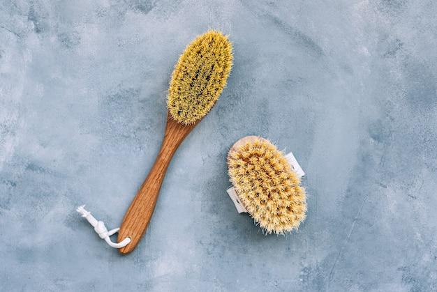 Drewniane szczotki do masażu suchego ciała na białym tle na niebieskim tle.