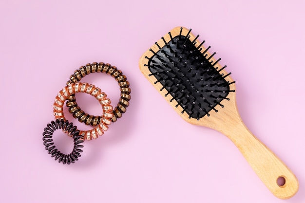 Drewniane szczotki do włosów, spirale do włosów na różowym tle