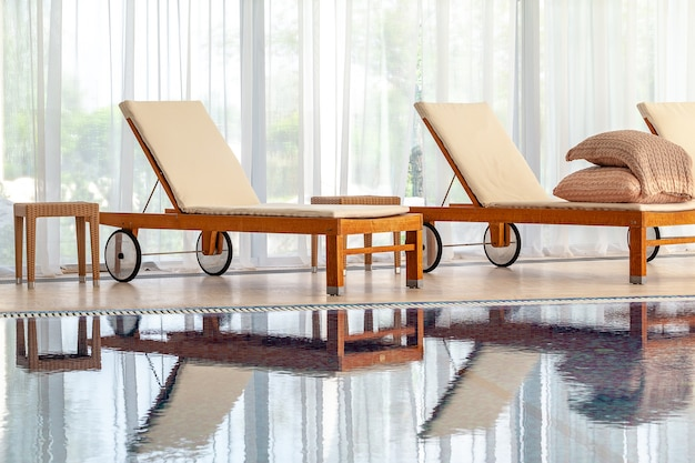 Drewniane szezlongi z materacami na tle szerokiego okna w domowym krytym basenie