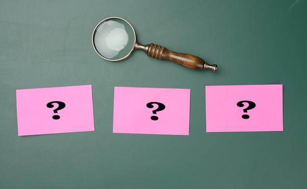 Drewniane szkło powiększające i białą kredą narysowane znaki zapytania na zielonej tablicy kredą. pojęcie znajdowania rozwiązań, prawdziwych lub fałszywych. odpowiedzi na pytania