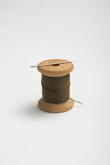 Drewniane szpule z nitką na solidnym tle. zabarwienie