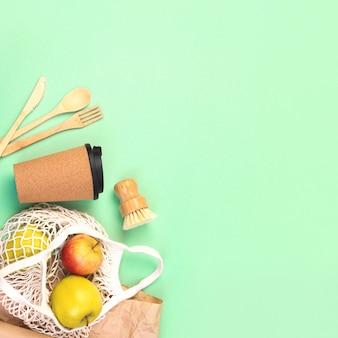 Drewniane sztućce wielokrotnego użytku, kubek z korka i torba na zakupy z jabłkami. szczotka do mycia naczyń i papier pakowy, ekologiczny widelec, nóż, łyżka na zielonym tle kwadratu mięty. koncepcja zero odpadów. miejsce.