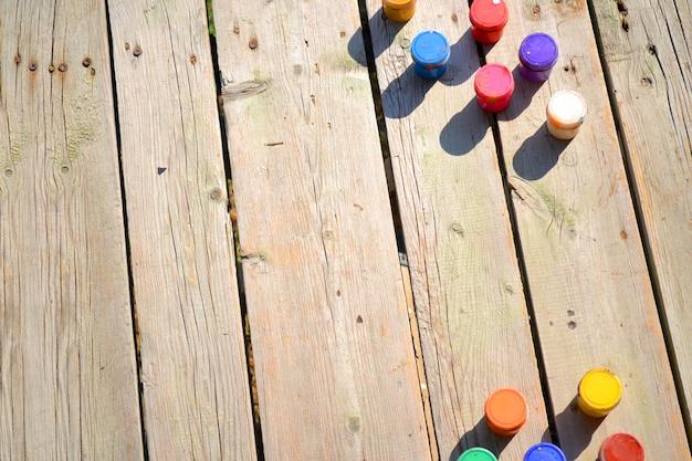 Drewniane tła i małe słoiki z gwaszem farby widok z góry w słoneczny dzień. tło, miejsce na tekst