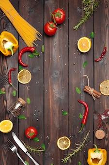 Drewniane tło do gotowania z rozrzuconymi ziołami i przyprawami