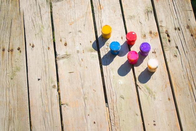 Drewniane tło i małe słoiki z farbą gwaszową