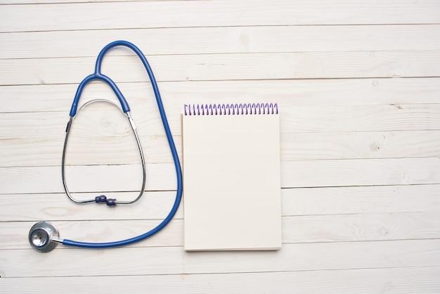 Drewniane tło stetoskop notatnik leczenie medycyna szpital. zdjęcie wysokiej jakości